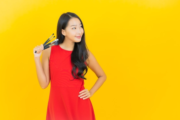 Portret piękna młoda azjatykcia kobieta z kosmetycznym pędzelkiem na żółtej ścianie