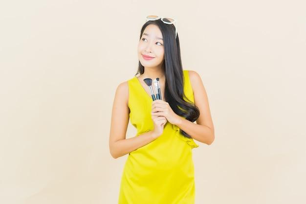 Portret piękna młoda azjatykcia kobieta z kosmetykami tworzą pędzel na ścianie koloru