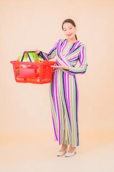 Portret piękna młoda azjatykcia kobieta z koszykiem z supermarketu na kolor