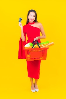 Portret piękna młoda azjatykcia kobieta z koszykiem z supermarketu