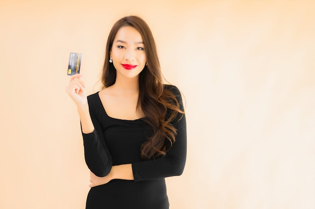 Portret piękna młoda azjatykcia kobieta z kredytową kartą