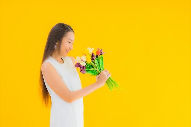 Portret piękna młoda azjatykcia kobieta z kwiatem