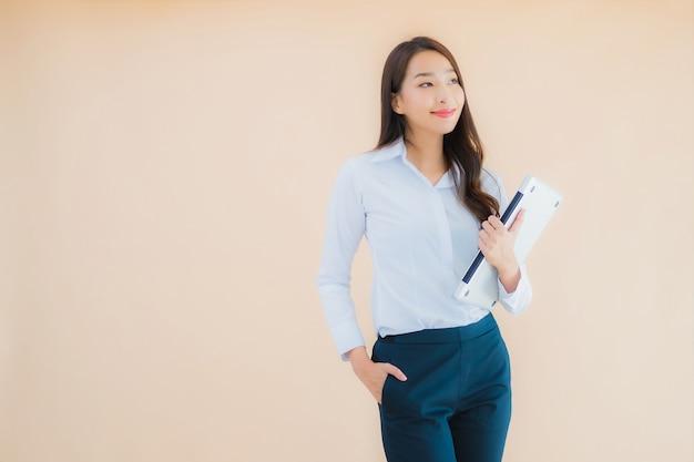 Portret piękna młoda azjatykcia kobieta z laptopa do pracy