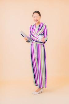 Portret piękna młoda azjatykcia kobieta z laptopa na kolor