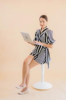 Portret piękna młoda azjatykcia kobieta z laptopem lub komputerem