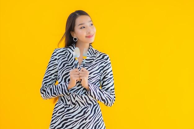 Portret piękna młoda azjatykcia kobieta z łyżką i widelcem gotowe do spożycia na żółto