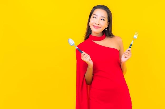 Portret piękna młoda azjatykcia kobieta z łyżką i widelcem gotowe do spożycia