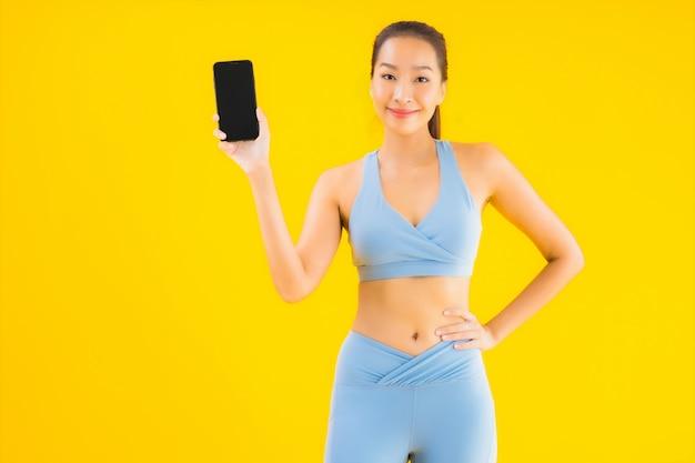 Portret piękna młoda azjatykcia kobieta z mądrze telefonem komórkowym na kolorze żółtym odizolowywającym