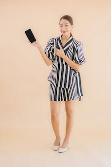 Portret piękna młoda azjatykcia kobieta z mądrze telefonem komórkowym