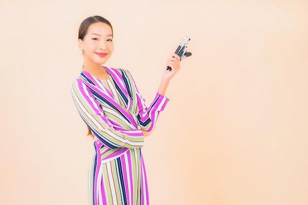Portret piękna młoda azjatykcia kobieta z makijażem pędzel kosmetyczny na kolor