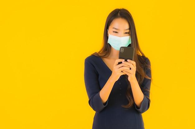 Portret piękna młoda azjatykcia kobieta z maską i telefonem