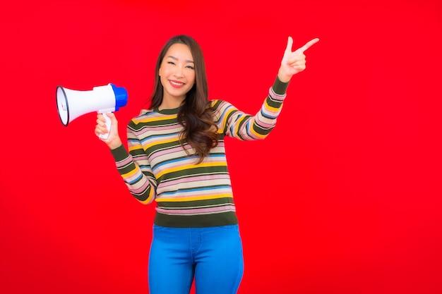 Portret piękna młoda azjatykcia kobieta z megafonem do komunikacji na czerwonej ścianie