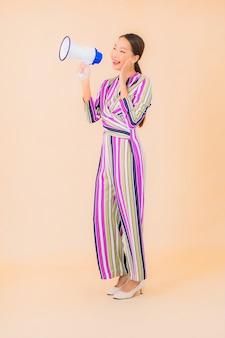 Portret piękna młoda azjatykcia kobieta z megafonem do komunikacji w kolorze