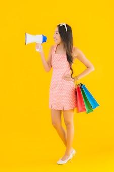 Portret piękna młoda azjatykcia kobieta z megafonem i torba na zakupy