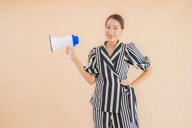 Portret piękna młoda azjatykcia kobieta z megafonem