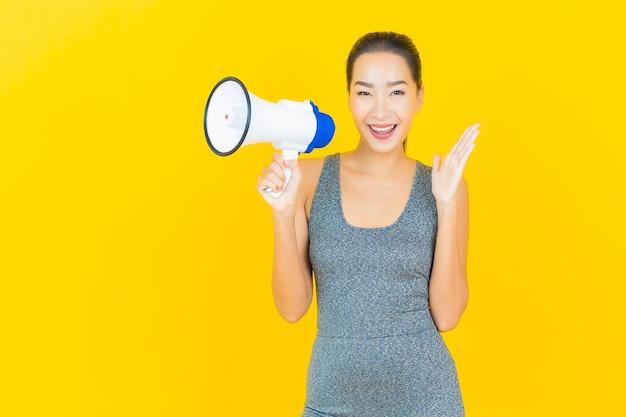 Portret piękna młoda azjatykcia kobieta z odzież sportową i megafon na żółtej ścianie