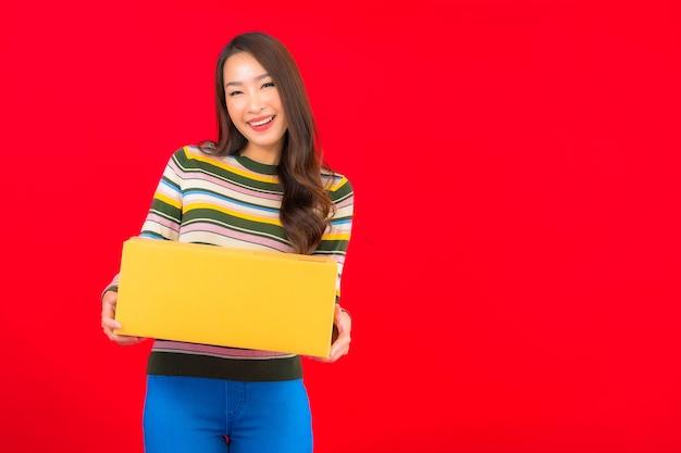Portret piękna młoda azjatykcia kobieta z paczką na czerwonej ścianie na białym tle