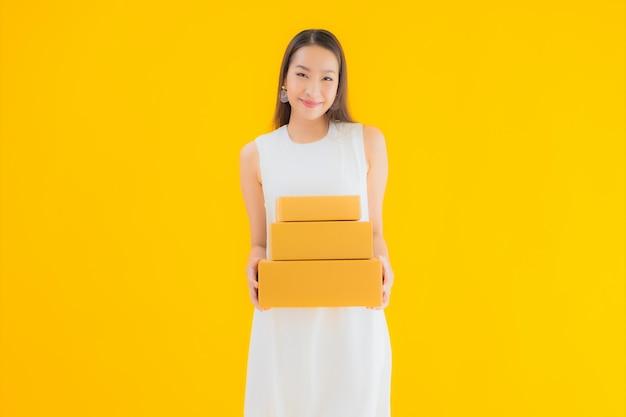 Portret piękna młoda azjatykcia kobieta z paczką