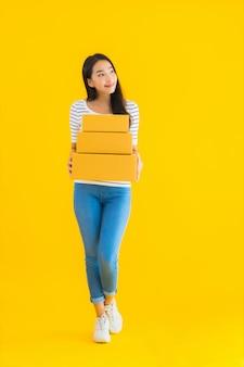 Portret piękna młoda azjatykcia kobieta z pakuneczka pudełkiem przygotowywającym dla wysyłać