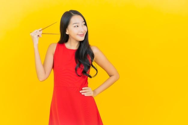 Portret piękna młoda azjatykcia kobieta z pałeczką gotową do spożycia na żółtej ścianie