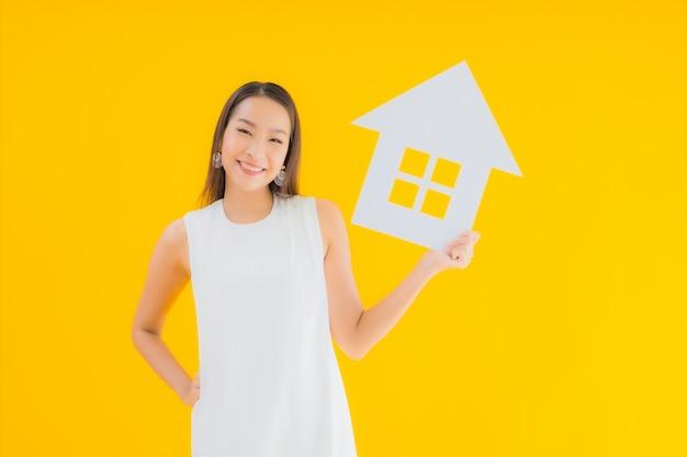 Portret piękna młoda azjatykcia kobieta z papierowym domem
