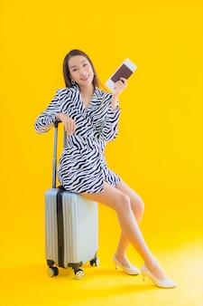 Portret piękna młoda azjatykcia kobieta z paszportem bagażowym i kartą pokładową na żółto