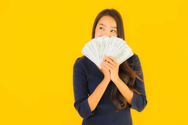 Portret piękna młoda azjatykcia kobieta z pieniądze i gotówką