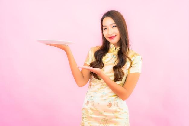 Portret piękna młoda azjatykcia kobieta z płytą na różowej ścianie