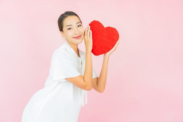 Portret piękna młoda azjatykcia kobieta z poduszką w kształcie serca na różowej ścianie