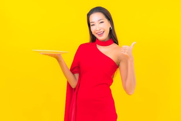 Portret piękna młoda azjatykcia kobieta z pustym naczyniem talerz