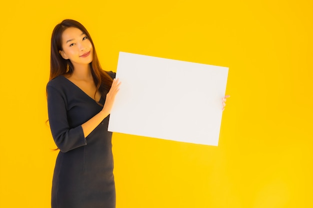 Portret piękna młoda azjatykcia kobieta z pustym plakatem