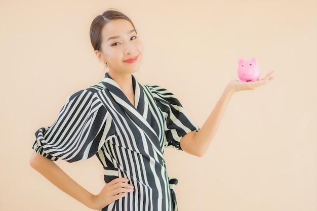 Portret piękna młoda azjatykcia kobieta z różowym prosiątko bankiem
