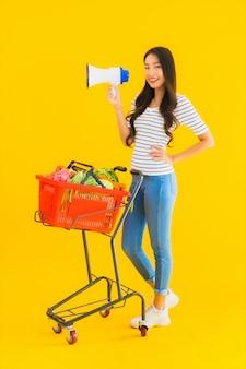 Portret piękna młoda azjatykcia kobieta z sklep spożywczy koszykową furą i megafonem