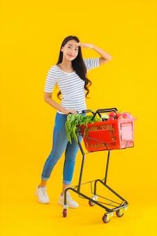 Portret piękna młoda azjatykcia kobieta z sklep spożywczy koszykową furą od supermarketa w zakupy centrum handlowym