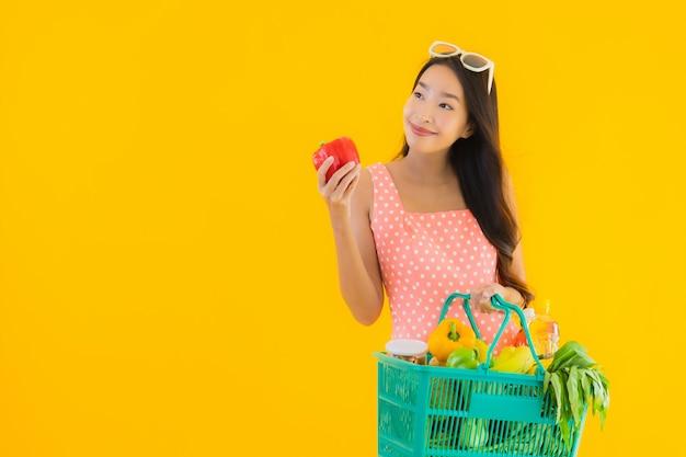 Portret piękna młoda azjatykcia kobieta z sklepem spożywczym w koszykowym zakupy od supermarketa
