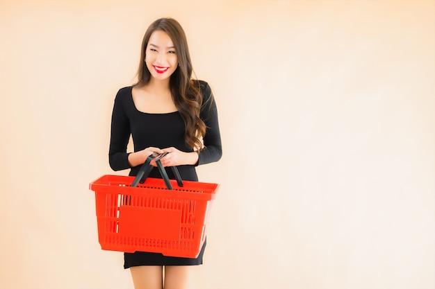 Portret piękna młoda azjatykcia kobieta z sklepu spożywczego koszem