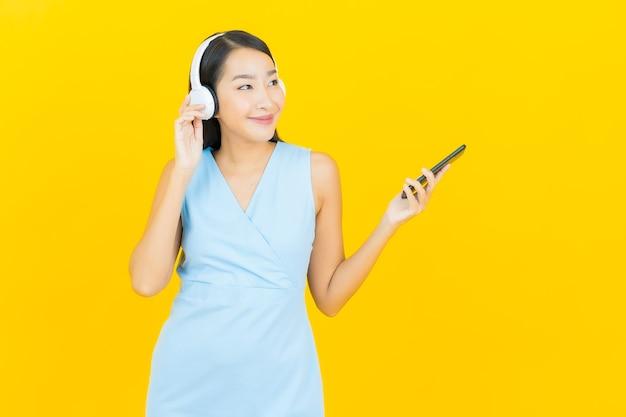 Portret piękna młoda azjatykcia kobieta z słuchawki i inteligentny telefon do słuchania muzyki na żółtej ścianie
