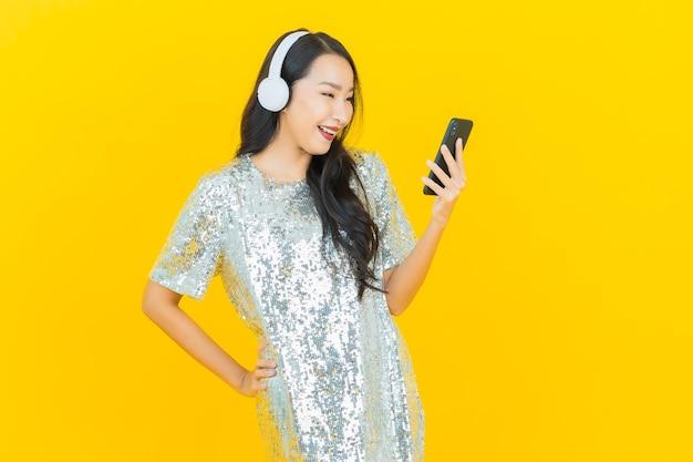 Portret piękna młoda azjatykcia kobieta z słuchawki i inteligentny telefon do słuchania muzyki na żółto