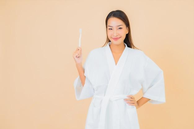 Portret piękna młoda azjatykcia kobieta z szczoteczką do zębów na beżu