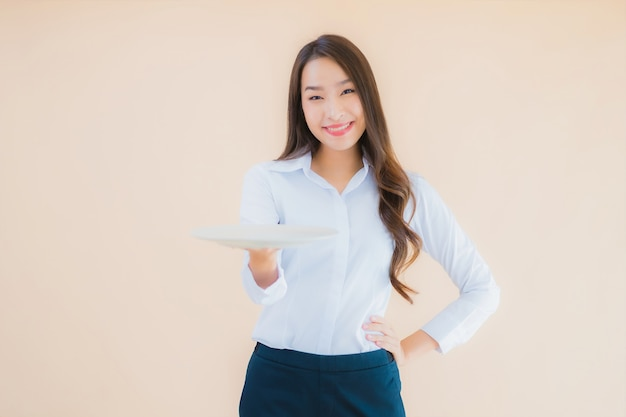 Portret piękna młoda azjatykcia kobieta z talerzem lub naczyniem
