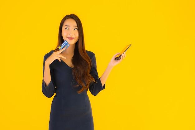 Portret piękna młoda azjatykcia kobieta z telefonem i kredytową kartą