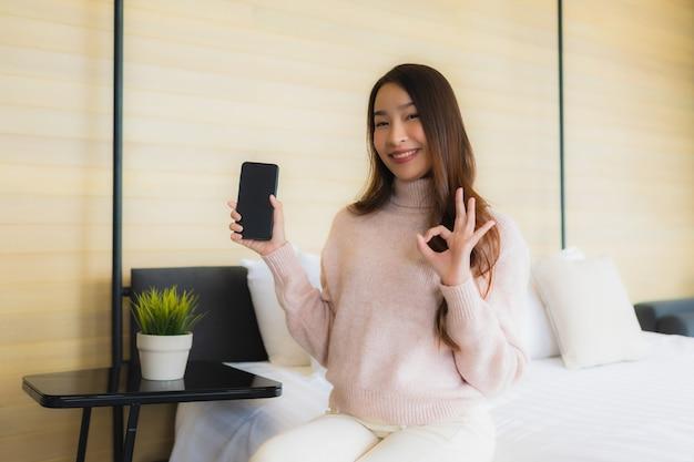 Portret piękna młoda azjatykcia kobieta z telefonem komórkowym na łóżku