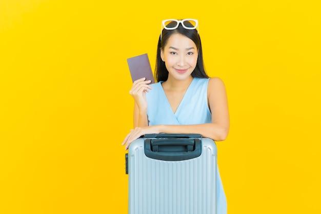Portret piękna młoda azjatykcia kobieta z torbą bagażową i paszportem gotowy do podróży