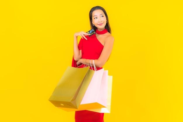 Portret piękna młoda azjatykcia kobieta z torbą na zakupy i kartą kredytową
