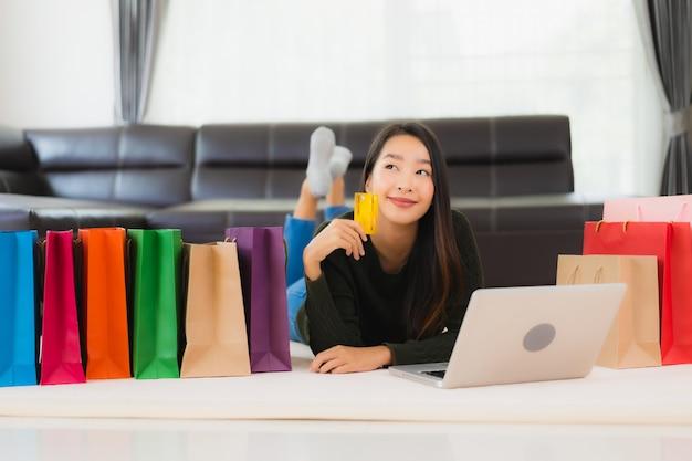 Portret piękna młoda azjatykcia kobieta z torba na zakupy i kredytową kartą