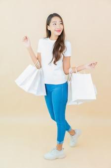 Portret piękna młoda azjatykcia kobieta z torbą na zakupy na beżu
