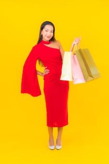 Portret piękna młoda azjatykcia kobieta z torbą na zakupy