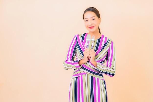 Portret piękna młoda azjatykcia kobieta z widelcem i łyżką gotową do spożycia na kolor