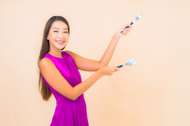 Portret piękna młoda azjatykcia kobieta z widelcem i łyżką gotową do spożycia na kolorowym tle