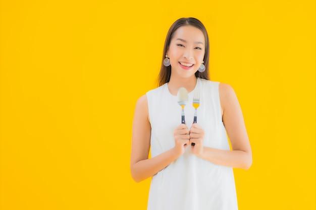 Portret piękna młoda azjatykcia kobieta z widelcem łyżką